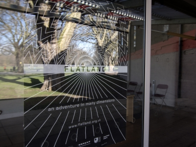 Image: A sideways shot of the poster for Flatland in black and white, inside a window frame. Blending into the image is a reflection of a large tree and park outside on a summery day.