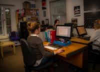 Three female team members sat working at desks in the Extant office, and poster from the Flatland production on the opposite wall.