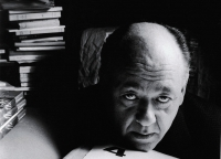 Absurd dramatist Eugene Ionesco rests his head on a pile of manuscript and journals, with more books stacked up high to his left.