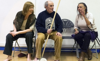 Maria Oshodi sits talking to actors Heather and John, who is holding a prop mop. Film about The Chairs tour, spring 2014