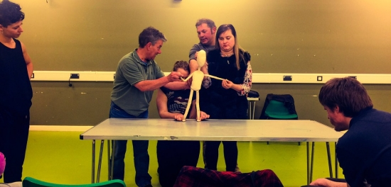 Participants look at and touch puppets, in workshop with artists of Meet Fred company before a show at mac Birmingham