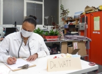A woman in doctor's outfit and face mask sits busy behind a desk on which a sign reads Dr Watt