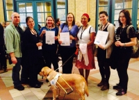 Group photo of the Chairs winners Louise, Anna and Beatrice holding certificates with 4 other members of the Extant team and Bella the dog.