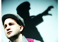 Close up of a young man wearing a cap, the shadow of a Nazi officer reaches menacingly in the background