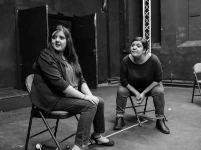 Image: Black and white photo. Two of the female youth theatre participants, one leaning forward on her chair and another turned to the side with hands in her lap, look with wide-eyed expressions at another performer who is speaking but out of shot.