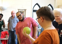 A group of young people in a brightly lit room giving a lot of attention to a grapefruit-sized ball.