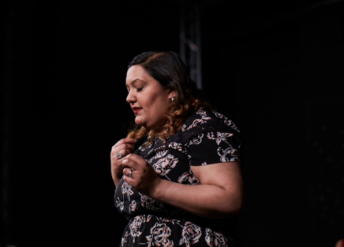 Side profile of a young south Asian woman against a black background. Her eyes are closed and both hands up towards her chest as she deliver