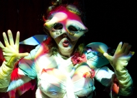 Burlesque image of Heather in a grotesque bodysuit with prosthetic boobs, a protruding half mask, rubber gloves and bright red pursed lips