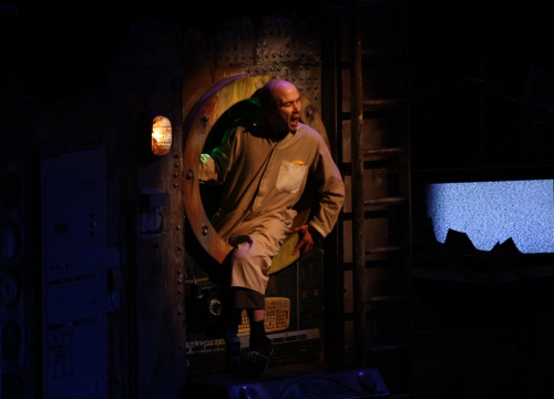 Image of Tim Gebbels as the Old Man in The Chairs, sitting in the porthole illuminated by the spotlight
