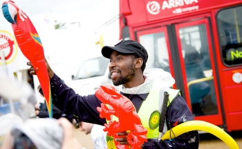 A man in dark blue mechanics uniform hands out brightly coloured inflatable animals, a red double decker bus is visible behind