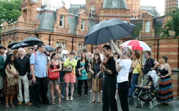 Japanese viola player with audience around him and umbrella over him. Film of an outdoor performance piece