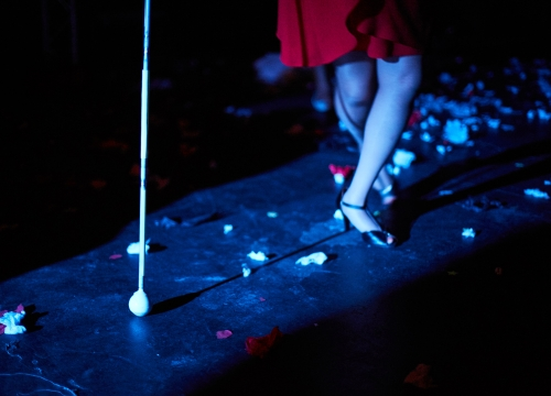 A close up of a performer's crossed legs (from the knee down) and her white cane as she moves sideways into a strip of light onstage. Pieces