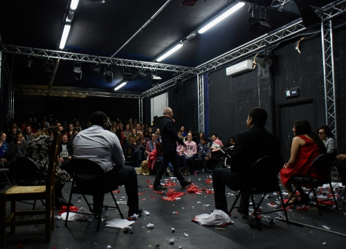 a shot from the back of the stage inside a blackbox space as the Unexpected youth theatre group, sat in a semicircle and director Shane walk
