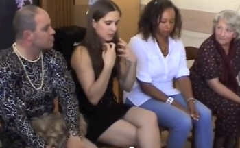 White female performer sits in a line next to other cast members, talking. Filmed discussion about her burlesque performance