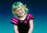 A girl aged 5 or 6 with platinum blonde hair in oversized, tinted glasses with leopard-print frames. She wears a pink and black dress.