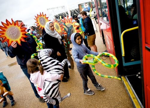 a crowd of children and parents getting ready to board the ComBUStion bus, with inflatable animals and large cut outs of fiery suns. The sid