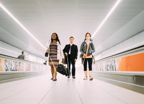 Three visually impaired people, two female, one male, walk towards camera, airport moving walkways either side of them.