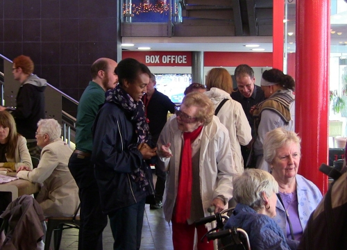 Various participants gather the foyer of Stratford Circus and talk in groups before a sharing event for intergenerational project, Spirit of