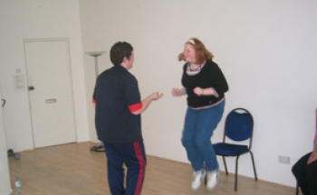 A white boy and girl use a skipping rope in a dance studio. Film of participation work