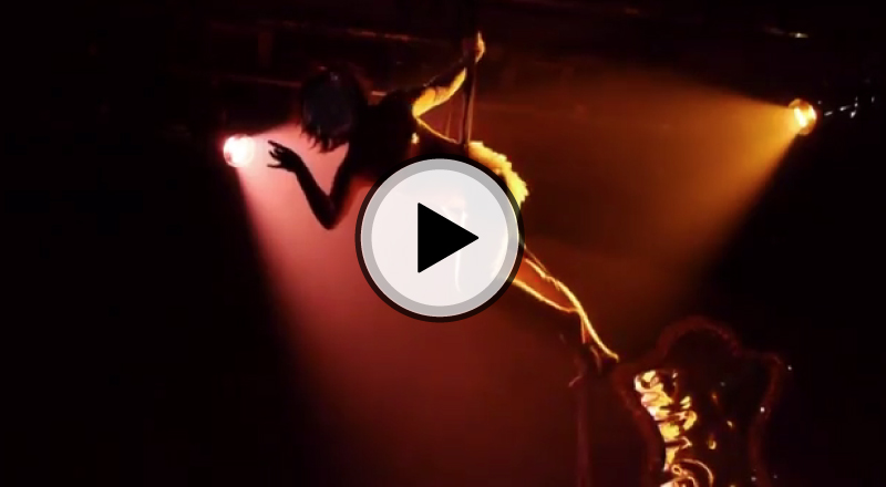 Clip from video - Amelia in burlesque costume is suspended in the air